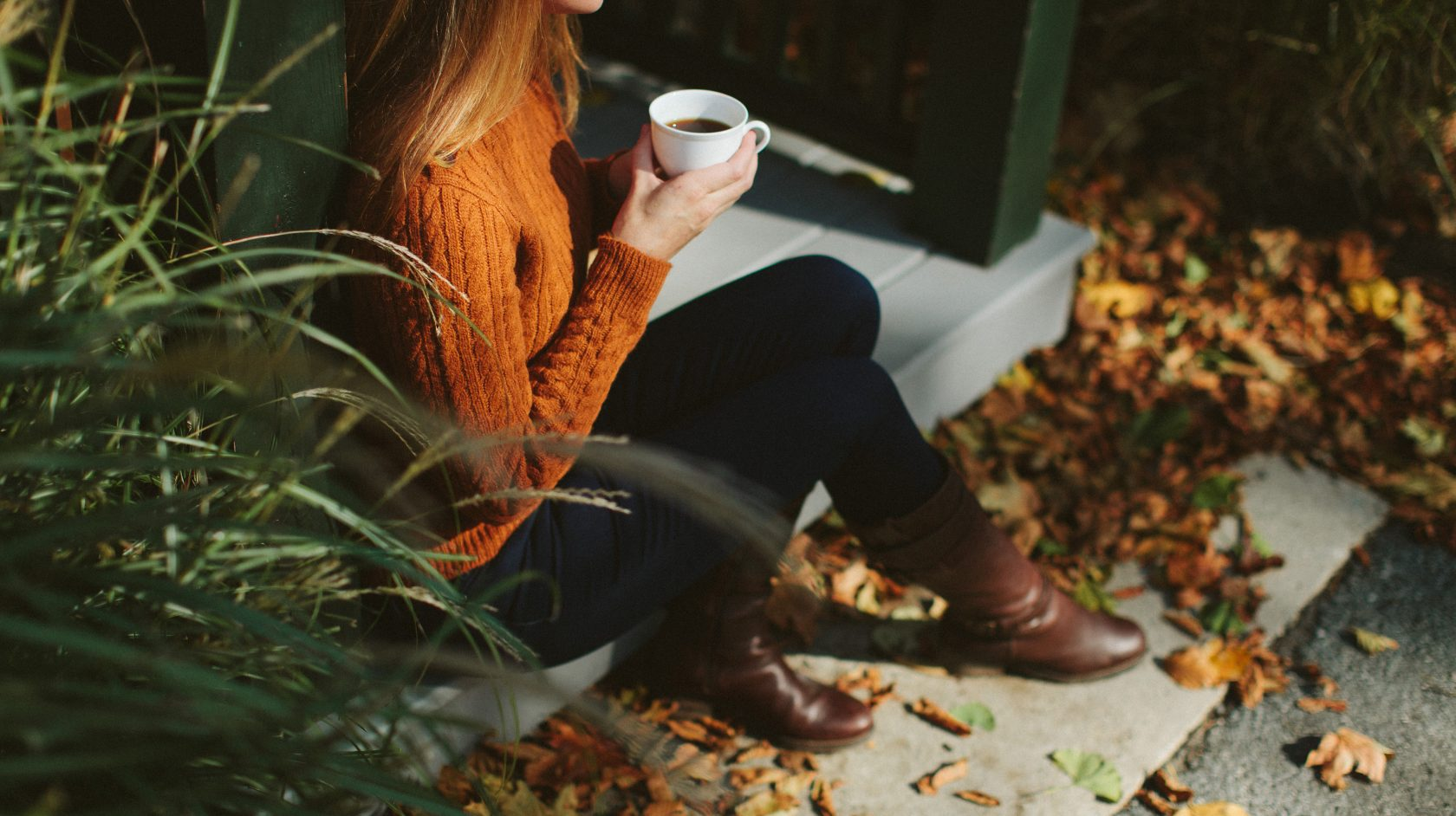woman drinking coffee sitting on stoop of Castle Hill Inn's cottage in the fall