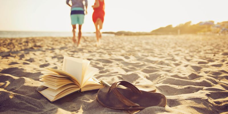 book and shoes thrown on sand while couple takes a walk on the beach near Castle Hill Inn in Rhode Island